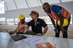 Three men looking into a notebook at a construction site