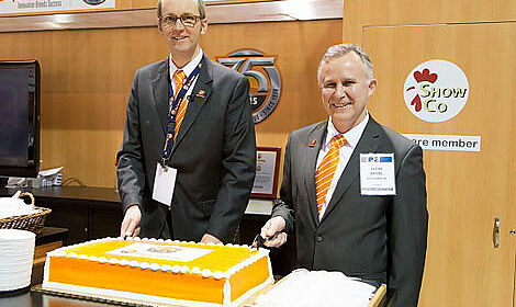 Celebrating 75 years of successful poultry systems with a huge anniversary cake.