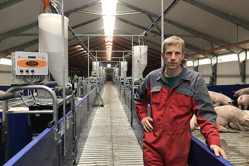 Farmer in a long aisle with pens to the left and to the right