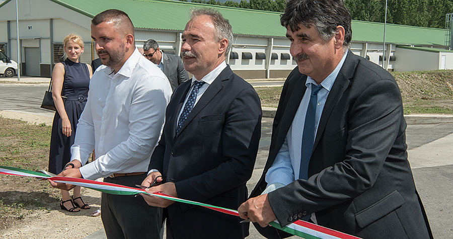 Three men cutting a ribbon